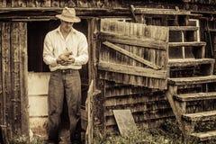 Jonge Landbouwer en een Kip stock foto