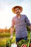 Jonge landbouwer met glimlach op het werk in tuin royalty-vrije stock foto's