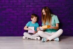 Jonge langharige moeder en zeven-jaar-oude zoon in overhemden en tennisschoenen die op de vloer zitten en een doos van giften hou stock foto's