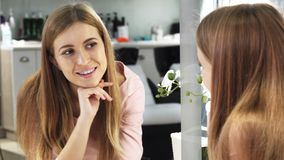 Jonge langharige mooie vrouw die in de spiegel schoonheidssalon bekijken royalty-vrije stock afbeeldingen