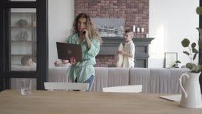 Jonge laptop die van de moederholding door celtelefoon proberen te spreken terwijl haar vier tienerzonen die araund het spelen me stock videobeelden