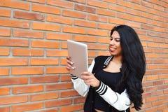 Jonge Latijnse vrouw die een tablet in openlucht gebruiken Royalty-vrije Stock Fotografie