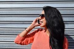 Jonge Latijnse vrouw die op de telefoon spreken Stock Foto