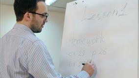 Jonge leraar die in glazen de oefeningen van het huiswerk op flipchart schrijven stock footage