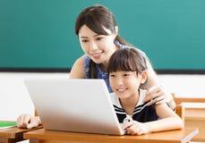 Jonge Leraar die kind met computerles helpen stock afbeeldingen