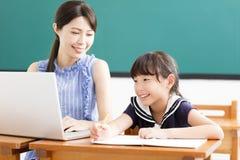Jonge Leraar die kind met computerles helpen stock afbeelding