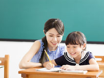 Jonge Leraar die kind met het schrijven van les helpen stock foto