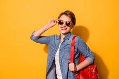 Jonge leuke dame met het richten van glimlach in modieuze zonnebril op stock afbeelding