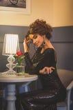 Jonge leuke donkerbruine dame met krullende haarzitting in koffie Royalty-vrije Stock Foto's