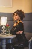 Jonge leuke donkerbruine dame met krullende haarzitting in koffie Royalty-vrije Stock Afbeeldingen