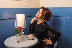 Jonge leuke donkerbruine dame met krullende haarzitting in koffie Stock Afbeeldingen