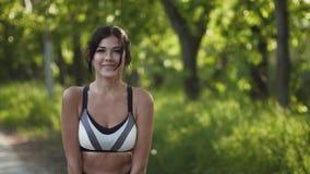 Jonge leuke jonge vrouw in sportkleding die en bij de camera stellen glimlachen de meisjesatleet verspreidt de schoonheid en de g stock footage