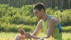 Jonge leuke mens die smartphone op groen gras tegen achtergrond van mooie aard in de zomer bekijken stock footage