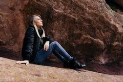Jonge Leuke Moderne Kaukasische Vrouw die voor de Massieve Natuurlijke Rode Muur van de Rotssteen buiten in Aard bij het Park van royalty-vrije stock afbeeldingen