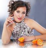 Jonge leuke vrouw met citrusvruchtenzitting Royalty-vrije Stock Afbeelding