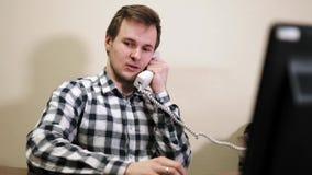 Jonge luie zakenmanzitting in bureau die op de telefoon spreken stock footage