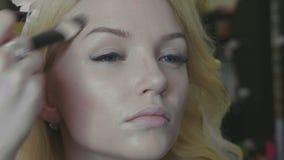 Jonge make-upkunstenaar die camouflagestift op het modelgezicht van ` toepassen s stock videobeelden