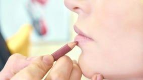 Jonge make-upkunstenaar die lippenstift op de modellippen van ` toepassen s stock foto's