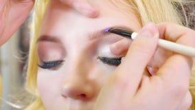 Jonge make-upkunstenaar die schoonheidsmiddelen op het modelgezicht van ` toepassen s stock fotografie