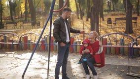 Jonge mamma en papa met een zuigeling die op de speelplaats spelen schommeling en carrousels in het park voor kinderen stock videobeelden