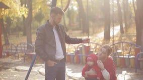 Jonge mamma en papa met een zuigeling die op de speelplaats spelen schommeling en carrousels in het park voor kinderen stock video