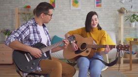Jonge man de gitarist onderwijst een jonge vrouw om gitaar te spelen stock video