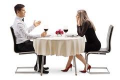 Jonge man die aan een jonge vrouw bij een restaurantlijst spreken stock foto's