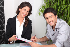 Jonge man die document en het jonge vrouw glimlachen ondertekent Royalty-vrije Stock Afbeelding