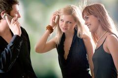 Jonge man die door mobiele telefoon en twee vrouwen spreekt die hem bekijken Royalty-vrije Stock Foto's