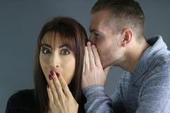Jonge man die een geheim vertellen aan een vrouw stock foto