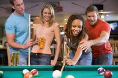 Jonge man die een jonge vrouw onderwijst om pool te spelen Stock Afbeeldingen