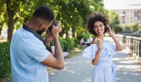 Jonge man die foto van mooie vrouw in park nemen stock fotografie