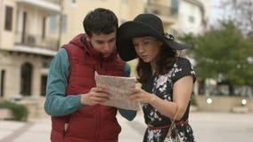 Jonge man die mooie vrouw helpen om manier aan hotel te vinden, die richting op kaart tonen stock footage