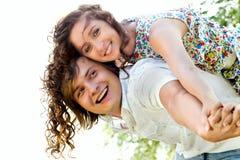 Jonge man die op de rug aan gelukkige vrouw geeft Royalty-vrije Stock Afbeelding