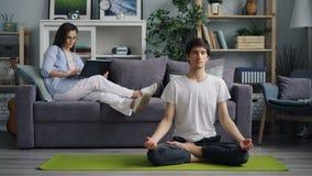 Jonge man die op yogamat mediteren terwijl vrouw die met laptop het glimlachen werken stock video