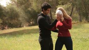 Jonge man die vrouw met masker helpen stock footage