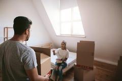 Jonge man dragende doos met vrouw op achtergrond in nieuw huis stock afbeeldingen
