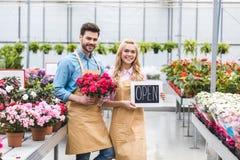 Jonge man en blondevrouw die Open raad houden door bloemen Stock Foto