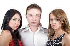 Jonge man en twee jonge vrouwen Stock Foto