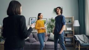 Jonge man en vrouw die aan makelaar in onroerend goed in nieuw huis met mooi binnenland spreken stock footage