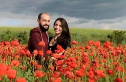 Jonge man en vrouw die datum op het gebied van papavers hebben Stock Foto