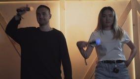 Jonge man en vrouw die in de ruimte dansen die van de zolderstijl lichtgevende bewegingssensoren en het glimlachen houden Het gel stock footage