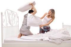 Jonge man en vrouw die een hoofdkussenstrijd op een bed hebben Royalty-vrije Stock Afbeeldingen
