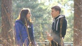 Jonge man en vrouw die in het park spreken stock footage
