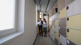 Jonge man en vrouw die investeringsproject status in gang van bedrijf bespreken stock footage