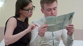 Jonge man en vrouw die kaart, het spreken, de vakantie van de planningsfamilie controleren stock video