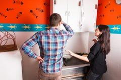 Jonge man en vrouw die keukengevallen overwegen en proberen te krijgen stock afbeelding