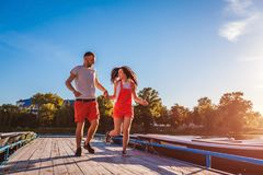 Jonge man en vrouw die langs het dok van de de zomerrivier lopen Paar die pret hebben bij zonsondergang Kerels het ontspannen stock afbeeldingen