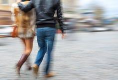 Jonge man en vrouw die onderaan de straat lopen Royalty-vrije Stock Foto's