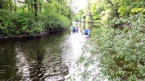 Jonge man en vrouw die op een rivier op een waterfiets drijven onder groene bomen stock footage